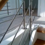 Wangentreppe in weiß, mit Eichenstufen und einem Geländer aus Edelstahl
